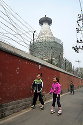 Young Chinese children inline skating in a small lane or hutong in Beijing China