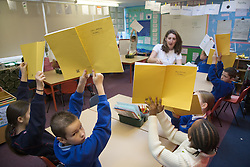 Primary school children holding up their exercises books to their teacher; in a lesson at school,