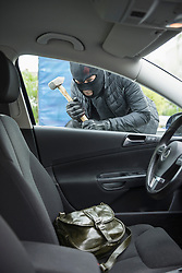Thief breaking into a car using hammer