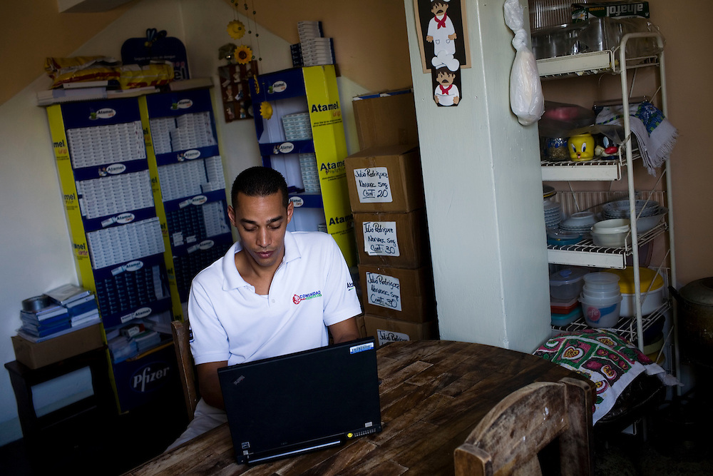 Julio Rodriguez, a sales rep for Pfizer, works in his home in Petare, one of the largest and most dangerous slums of Caracas.  Pfizer is trying to increase their market share in the slums and are targeting clinics, hospitals and pharmacies, sending sales representatives like Julio to far reaches of the slums.  His house is full with drug samples that he distributes to doctors.