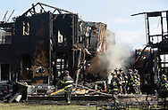 Salisbury Mills firefighters walk behind a house destroyed by a fire on Independence Drive in Vails Gate on Friday, Aug. 16, 2013.