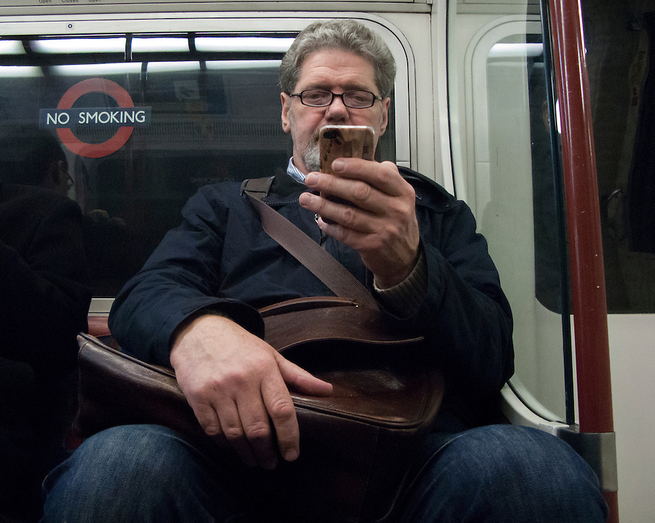 Portrait of a man on the London Underground network looking at his mobile device