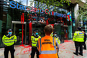 """A legal observer take notes as XR activists remain sat on the doors of the bank Standard Chartered, which has been covered in red paint during an Extinction Rebellion climate change protest in the city of London on Friday, 27 Aug 2021. This is their fifth day of an ongoing two-week disruption protest campaign """"The Impossible Rebellion"""". (VX Photo/ Vudi Xhymshiti)"""