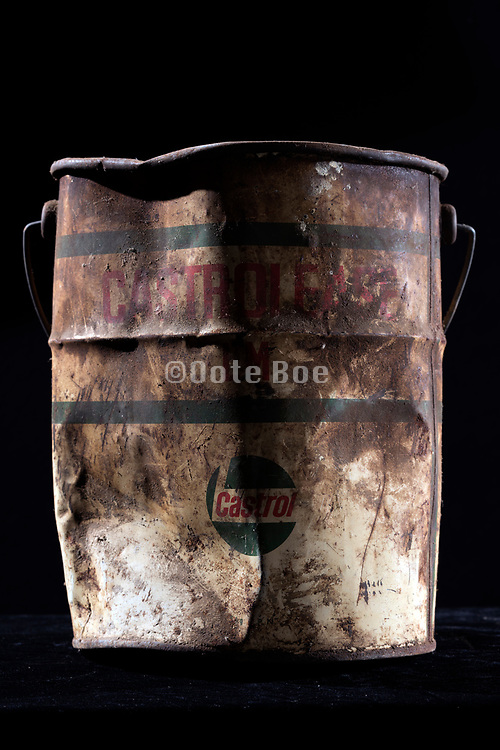 rusted and dented Castrol brand grease bucket