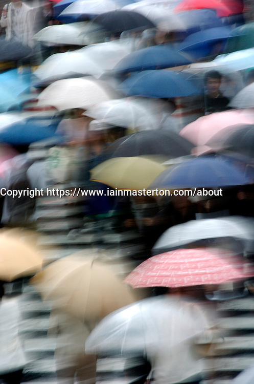 Many umbrellas in the rain in central Tokyo Japan - motion blur