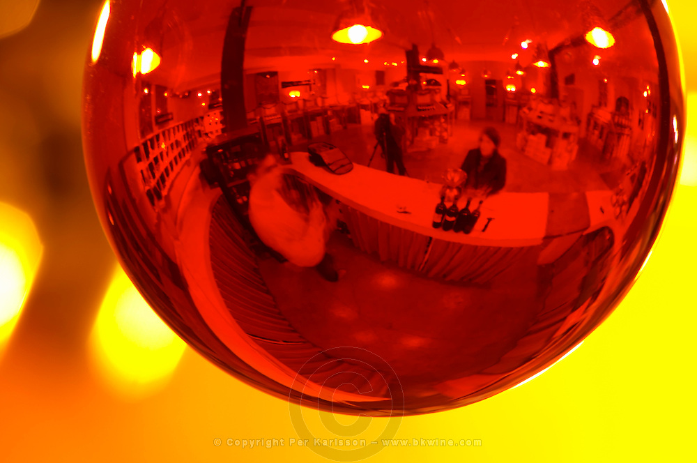 Domaine Gerard Bertrand, Chateau l'Hospitalet. La Clape. Languedoc. Tasting wine. Reflection in a red glass Christmas decoration ball. Fish-eye. France. Europe.