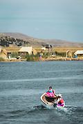Woman taking child to school, Floating islands on Lake Titicaca, Puno, Peru, South America