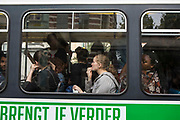 Many passengers travel on a De Lijn electric tram in Ghent, Belgium.