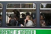 Many passengers travel on a De Lijn electric tram in Ghent, Belgium.