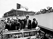 Assistant Manager Maurice Setters waves the Tricolour to a delighted crowd as the bus sets off for Dublin city centre.<br /> 19 June 1988