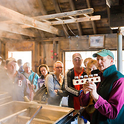 Brian Folsom explains the different grades of maple syrup to visitors at Folsom's Sugar House in Chester, New Hampshire.