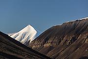 The montain in the middle, whith snow, is called Soleietoppen, and is located on Spitzbergen. The montain to the right is called Carl Lundhfjellet | Den snøkledde fjelltoppen heter Soleietoppen og ligger i Bolterdaled ved Adventsdalen ved Longyearbyen på svalbard. Fjellet til høyre er Carl Lundhfjellet.