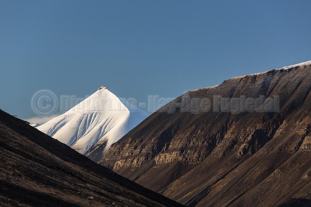 The montain in the middle, whith snow, is called Soleietoppen, and is located on Spitzbergen. The montain to the right is called Carl Lundhfjellet   Den snøkledde fjelltoppen heter Soleietoppen og ligger i Bolterdaled ved Adventsdalen ved Longyearbyen på svalbard. Fjellet til høyre er Carl Lundhfjellet.