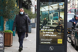 © Licensed to London News Pictures. 26/03/2021. London, UK. A man wearing a protective face covering walks past the government's 'Every bit of space is making a difference' poster in north London as MPs voted to extended emergency Covid-19 powers for another 6 months. The next key date for restrictions easing is Monday 29 March 2021, when the 'Stay at Home' guidance will be dropped. Photo credit: Dinendra Haria/LNP