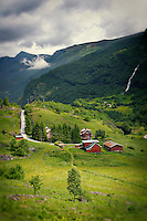 Small red houses lie in the mountainous countryside of Flam, Norway in the Fjords