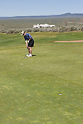 Vertical of golfer with residence in background