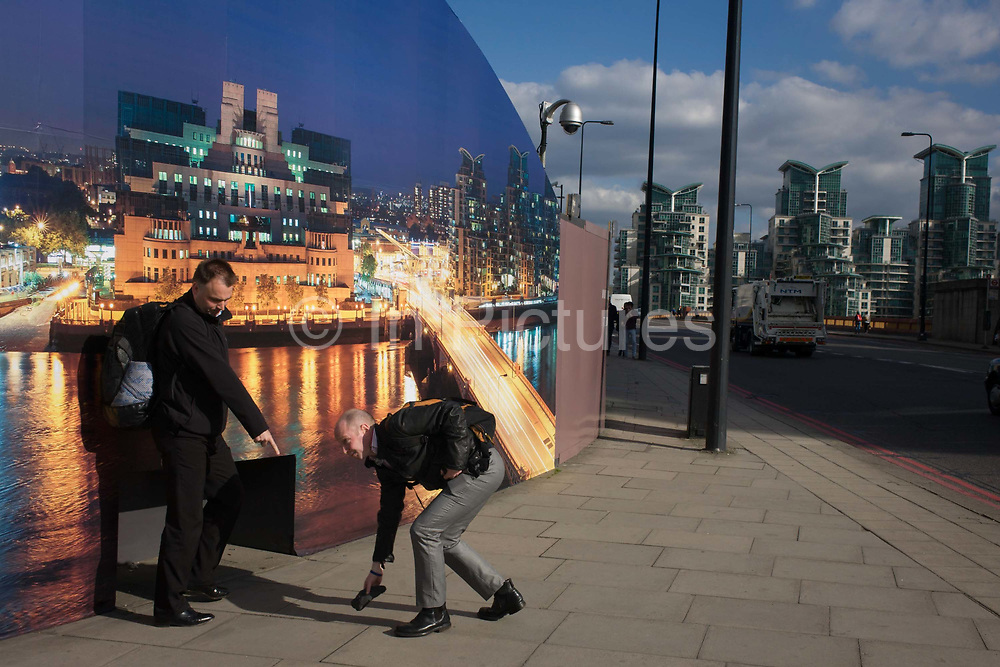 """A kind stranger picks-up a hat belonging to another pedestrian by a construction hoarding, a night time panorama of the Thames south bank, featuring the HQ of the intelligence service (MI6) and adjacent apartments across the river in Vauxhall. Under the gaze of a CCTV camera, the gentleman retrieves the item for another (unseen) person as his friend points to alert its owner. <br /> The temporary hoarding will stay in place for the time that the company's new residential riverfront apartments are under construction. In the image, the building at Vauxhall Cross, is located at 85 Albert Embankment beside Vauxhall Bridge. It is known within the intelligence community as """"Legoland"""" and """"Babylon-on-Thames""""."""