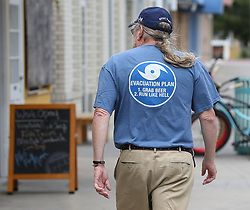 Local resident John Branigan, 65, one of the few islanders choosing to remain and ride out Hurricane Irma, makes his way down a deserted sidewalk in the business district wearing a shirt bearing his evacuation plan on Saturday, September 9, 2017, on Tybee Island, Ga. Photo by Curtis Compton/Atlanta Journal-Constitution/TNS/ABACAPRESS.COM
