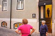 "Inhabitants of Rua Nova do Loureiro passing in front of hotel ""Casa das Janelas com Vista"", in Bairro Alto district, in Lisbon."
