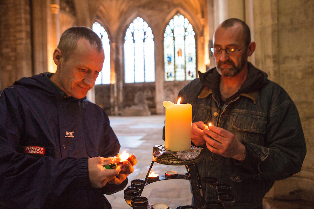 Rob and Ian lighting candles and praying inside Peterborough cathedral. They were both recently living on the streets of Peterborough for a number of years.  With belief in their faith and the help of Hope into Action they are now settled into safe and secure housing and are building connections with their families. Peterborough, Cambridgeshire. UK