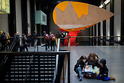 Art visitors and the textiles and language-themed sculpture entitled 'I Don't Know. The Weave of Textile Language' by American artist Richard Tuttle in Tate Modern's Turbine Hall. Tate Modern's Turbine Hall has played host to some of the world's most striking and memorable works of contemporary art. Now, this vast space welcomes the largest work ever created by renowned American sculptor Richard Tuttle (born 1941).  this newly commissioned sculpture combines vast swathes of fabrics designed by the artist from both man-made and natural fibres in three bold and brilliant colours.