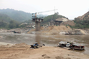 A new road bridge is currently under construction by the China Road Bridge Corporation over the Mekong river where it borders Oudomxay and Sayaboury provinces, Pak Beng, Lao PDR. Meanwhile rickety car ferries take local people and their motorbikes, cars and lorries, backwards and forwards across the river.