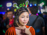 """31 DECEMBER 2012 - BANGKOK, THAILAND:  A Thai television reporter wears a 2013 hat during her """"stand up"""" report at the New Year's Eve party and countdown in Ratchaprasong Intersection in Bangkok. The traditional Thai New Year is based on the lunar calender and is celebrated in April, but the Gregorian New Year is celebrated throughout the Kingdom, especially in larger cities and tourist centers, like Bangkok, Chiang Mai and Phuket. The Bangkok Countdown 2013 event was called ?Happiness is all Around @ Ratchaprasong.? All of the streets leading to Ratchaprasong Intersection were closed and the malls in the area stayed open throughout the evening.  PHOTO BY JACK KURTZ"""