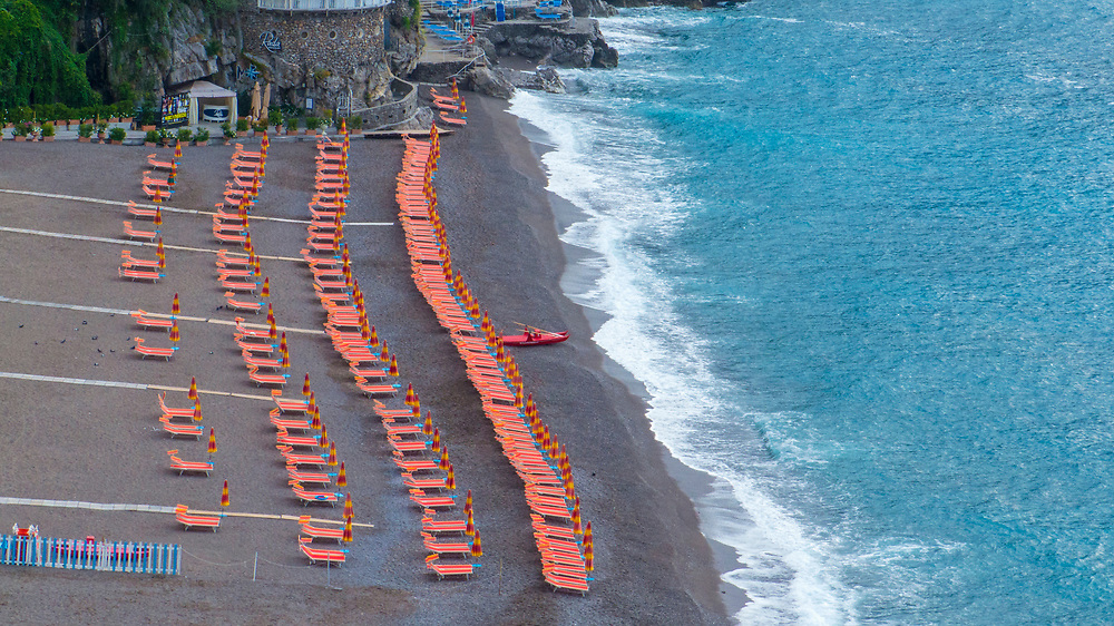 Colorful Beach umbrellas and chairs on beach in Positano, Italy