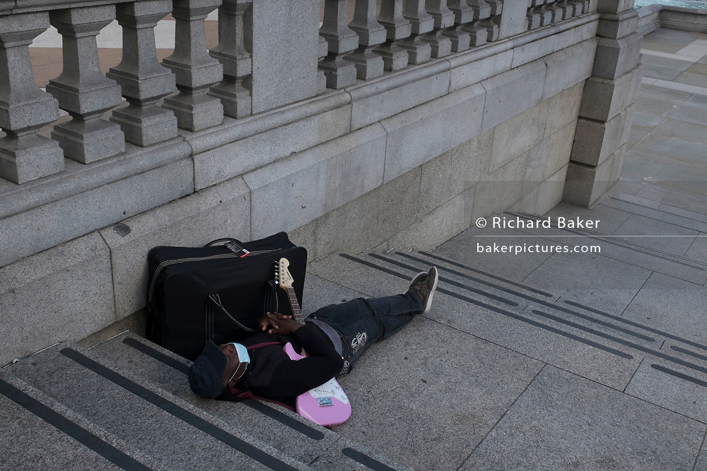 With a further 89 UK covid victims in the last 24hrs, bringing the total victims to 43,995 during the Coronavirus pandemic, pubs, restaurants, hairdressers and some art galleries will open again on Saturday 4th July. A street busker wearing a face mask and clutching his pink guitar, sleeps on the steps of Trafalgar Square, on 2nd July 2020, in London, England.