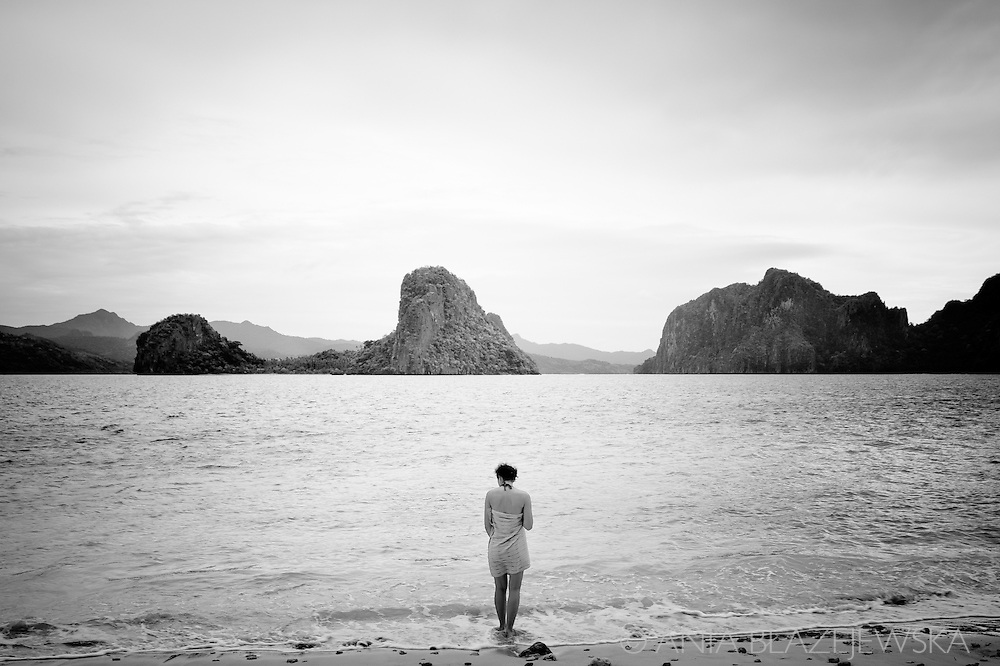 Philippines, El Nido. A woman on one o the beautiful beaches of the Bacut Archipelago.