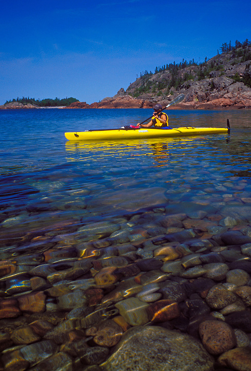 A sea kayaker cruises over Lake Superior cobblestones while paddling in Pukaskwa National Park near White River, Ontario.