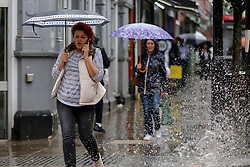© Licensed to London News Pictures. 14/09/2021. London, UK. A car splashes rain water as a woman shelters under an umbrella during rainfall in north London. A yellow weather warning for heavy rain is in place in London and parts of South East England. Photo credit: Dinendra Haria/LNP