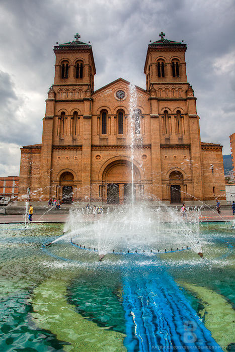 A spanish church next to a fountain in downtown Medellin, Colombia.