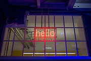A neon Hello sign in the window of a corporate office entrance in central London. Glowing in red lettering, the word of popular greeting is centred in the entrance of this generic company offices. Saturated blue ambient and artificial light is all around modern minimalist architecture and design.