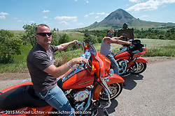 Jim Curtis and Jesse Fischer of Wisconsin stopped along highway 79 near Sturgis with Bear Butte in the background during the 75th Annual Sturgis Black Hills Motorcycle Rally.  SD, USA.  August 6, 2015.  Photography ©2015 Michael Lichter.