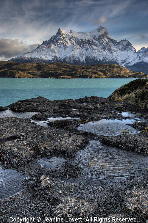 HDR high dynamic range photo combing two exposures. Lava rock pools in foreground with Patagonia lake and mountains in the back ground.