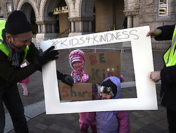 """December 10, 2016 - Washington, DC, USA - MAYA, 5 and ZOE, 1 have their picture taken inside frame of ''Photo Booth'' (Father asked not to use last name).  Holding sign is SAM REGGIO, left, and LOGAN WORSLEY. Children's Rally for Kindness takes place at Trump International Hotel in Washington DC on December 10, 2016 organized by the Takoma Parents Action Coalition.  According to their FaceBook page, it was a call to President-elect Donald Trump: ''to remember these lessons as he prepares to take office and implement policies that will affect the lives of children and families across our diverse nation.''.''All over the world, across cultures and countries, children learn the same basic lessons: .Ã'be kind,Ã"""" .Ã'tell the truth,Ã"""" .Ã'be fair,Ã"""" .Ã'respect everyone,Ã"""" .Ã'treat others the way you want to be treated,Ã"""" .Ã'donÃ•t touch others if they donÃ•t want to be touched. (Credit Image: © Carol Guzy via ZUMA Wire)"""