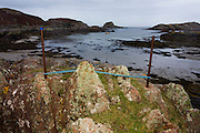 Rope and rocks in remote bay at Kintra, Isle of Mull, Scotland. The name comes from the Gaelic for 'end of the beach', 'Ceann Tràgha'. It was founded by the 5th Duke of Argyll to provide an income for himself and his tenants through fishing. Originally cottages with thatched roofs did not have gable ends or chimneys but this one has one gable and with a chimney attached. http://www.ambaile.org.uk/en/item/item_photograph.jsp?item_id=22178