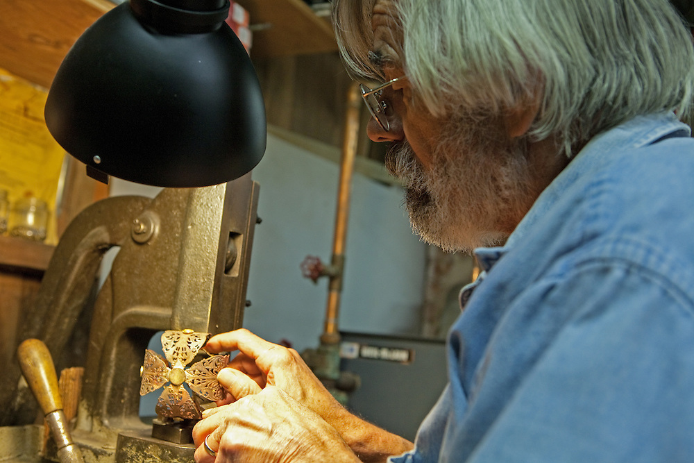 Rick Martin using a 19th-century hand press to rivet half-arches to the circlet, or headband, of a crown.