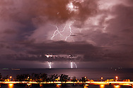 Cloud-to-ground lightning strikes the southern side of Biscayne Bay during a nocturnal thunderstorm in Miami, Florida. The Rickenbacker Causeway is visible in the foreground. WATERMARKS WILL NOT APPEAR ON PRINTS OR LICENSED IMAGES.