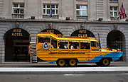 Duck Tours vehicle passes the Ritz Hotel in central London. Duwk amphibious vehicles drive out of the river onto dry land making for a unique tour around London by road and river.
