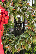 A stone garden fountain framed by a Christmas wreath on Meeting Street in Charleston, SC.