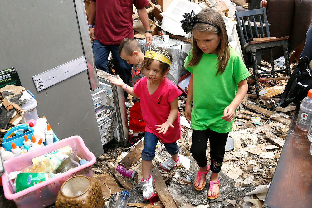 Kathryn Stephan, 4, (L) shows her neighbor Hannah Osborne her tornado-destroyed home for the first time since the storm on 6th Avenue in Moore, Oklahoma May 23, 2013. The tornado was the strongest in the United States in nearly two years and cut a path of destruction 17 miles long and 1.3 miles wide. REUTERS/Rick Wilking (UNITED STATES)