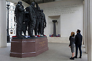 A young couple admire the Bomber Command War Memorial on 16th March 2017, in Green Park, London, England. The 9-foot (2.7 m) bronze sculpture of seven aircrew, designed by the sculptor Philip Jackson look as though they have just returned from a bombing mission and left their aircraft. The figures represent L-R: Navigator, Flight Engineer, Mid-upper gunner, Pilot, Bomb aimer, Rear gunner and Wireless operator. The Royal Air Force Bomber Command Memorial is a memorial in Green Park, London, commemorating the crews of RAF Bomber Command who embarked on missions during the Second World War. The memorial was built to mark the sacrifice of 55,573 aircrew from Britain, Canada, Czechoslovakia, Poland and other countries of the Commonwealth, as well as civilians of all nations killed during raids. Queen Elizabeth II unveiled the memorial on 28 June 2012, the year of her Diamond Jubilee.