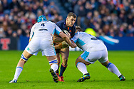 Mark Bennett (#13) of Edinburgh Rugby is tackled by Scott Cummings (#4) and Oli Kebble (#1) of Glasgow Warriors during the 1872 Cup second leg Guinness Pro14 2019_20 match between Edinburgh Rugby and Glasgow Warriors at BT Murrayfield Stadium, Edinburgh, Scotland on 28 December 2019.