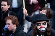 Demonstrator dressed as a banker / clown in a traditional bowler hat. Student Demonstration closes Oxford Street in London. Young people protest against many different government policies at this demonstration which included a sit down protest blocking Oxford Circus.