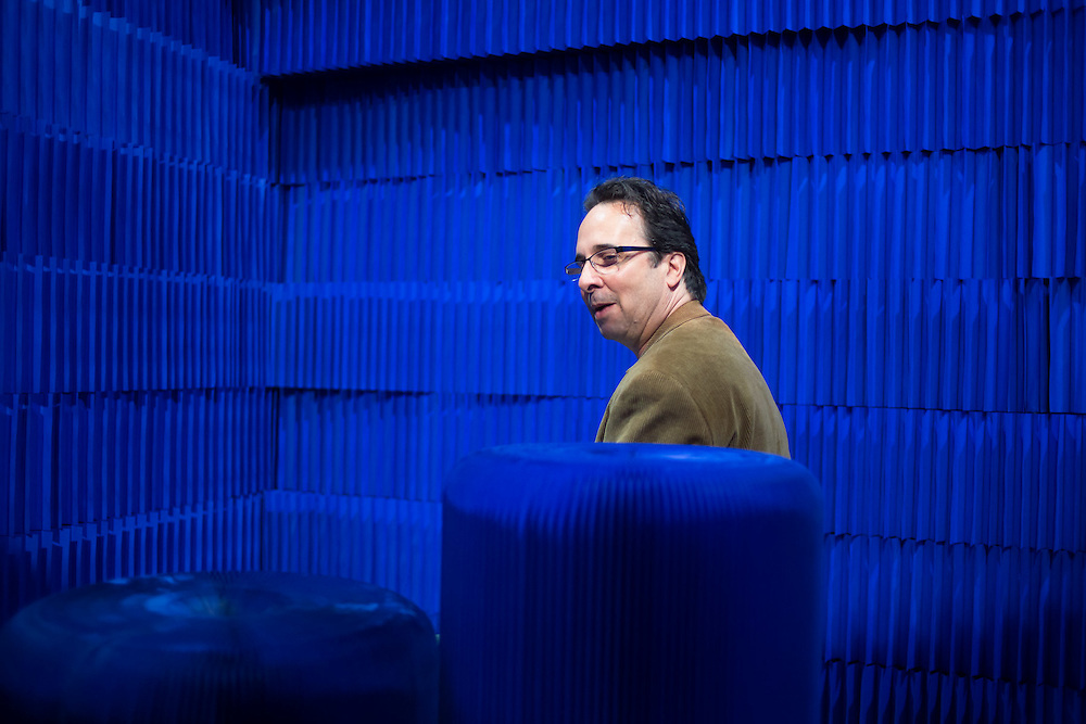 A man in the folded paper sound booth of Molo. The paper cylinders house speakers which are playing a composition by Ethan Rose.