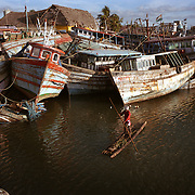 A fisherman ekes out a living in Nagappattinam, in the southeastern coast of India. Behind him are boats smashed by the tsunami. .The December 26, 2004 tsunami killed thousands of people along this coast, smashing boats, roads and houses and tearing thousands of families apart. .Picture taken February 2005 in Nagapptinam, Tamil Nadu, India, by Justin Jin