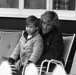 The Princess of Wales sits with her four year old son Prince William on her lap, watching the Prince of Wales play polo at Smith's Lawn, Windsor.