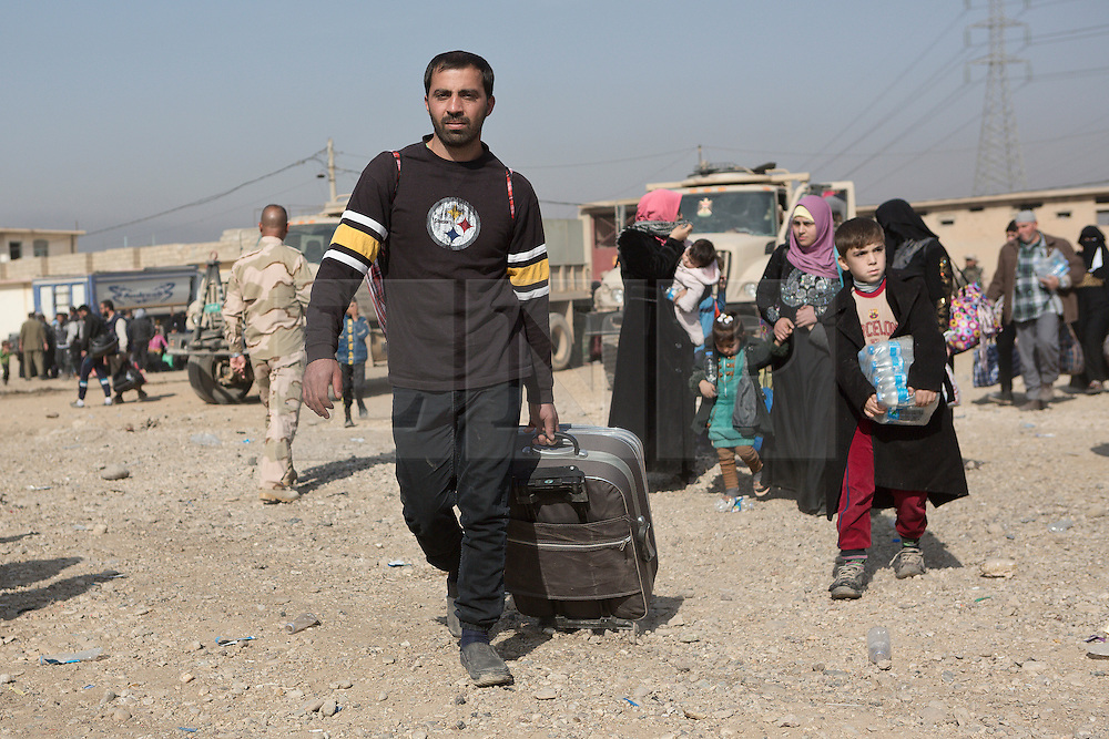 Licensed to London News Pictures. 11/11/2016. Mosul, Iraq. Iraqi refugees, who have escaped fighting in Mosul, walk with bags in the city's Hay Intisar district on the south east of the city. The district was taken by Iraqi Security Forces (ISF) around a week ago and, despite its proximity to ongoing fighting between ISF and ISIS militants, many residents still live in the settlement.<br /> <br /> The battle to retake Mosul, which fell June 2014, started on the 16th of October 2016 with Iraqi Security Forces eventually reaching the city on the 1st of November. Since then elements of the Iraq Army and Police have succeeded in pushing into the city and retaking several neighbourhoods allowing civilians living there to be evacuated - though many more remain trapped within Mosul.  Photo credit: Matt Cetti-Roberts/LNP